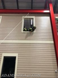 Firefighter Becky Mellinger prepares to dive out the window while simultaneously setting the hook to here bailout kit into the wall at the inner corner of the window sill.