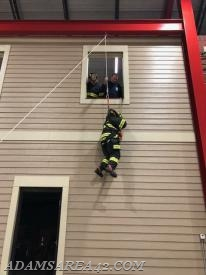 The rope line attached above on the beam is merely a safety belay. Firefighter Mellinger's weight is supported by the smaller line seen in the lower right corner of the window.