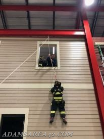 Utilizing the controlled descent device, Firefighter Mellinger begins to lower herself to the ground.